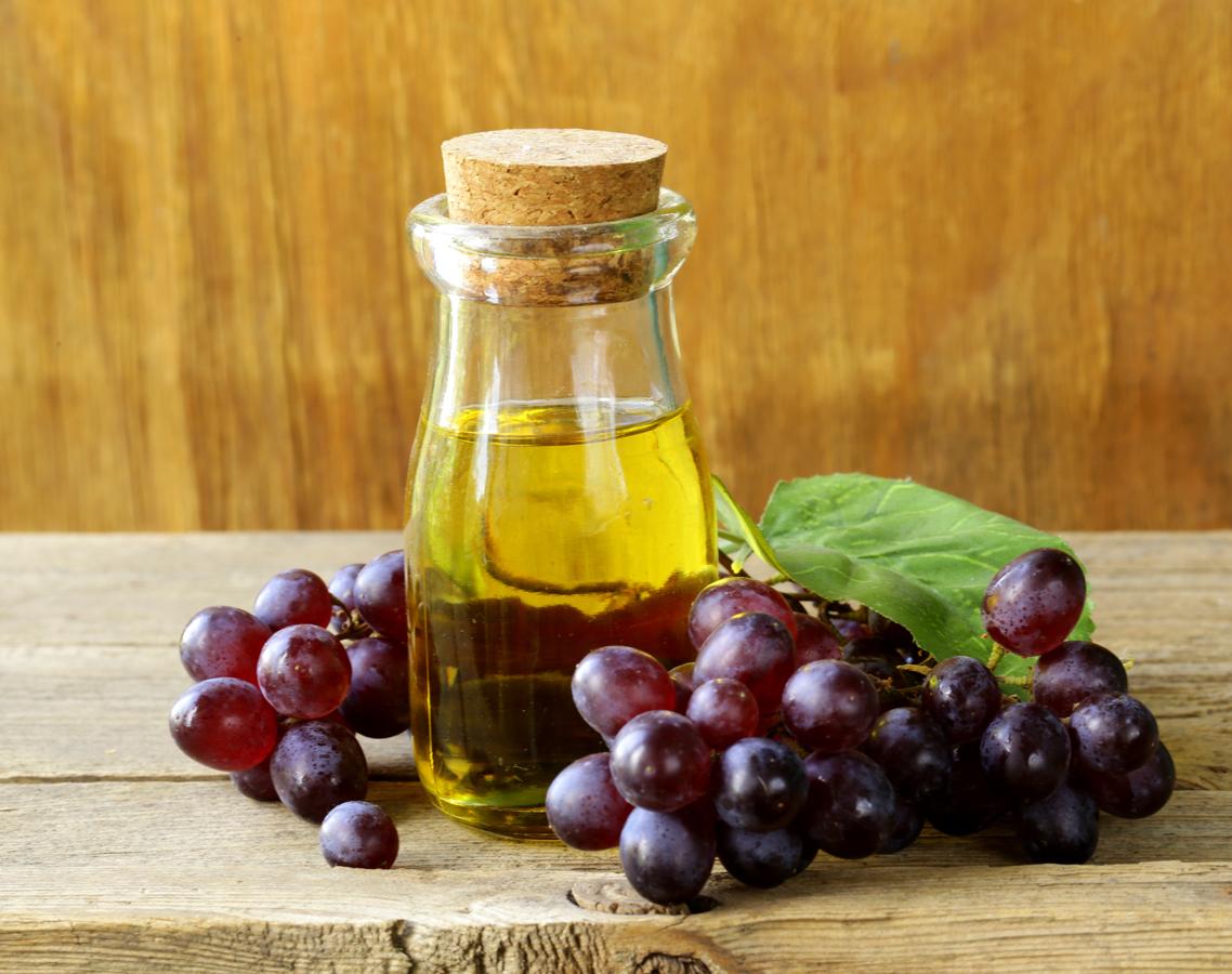виноград и бутылка с олифой